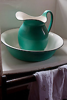 A green and white jug and basin in one of the bedrooms
