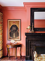 Chinese ancestor paintings are hung on walls lacquered in deep coral in the living room; an antique Dutch mirror hangs above a massive Flemish inspired custom fireplace.