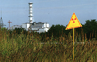 "UKRAINE, Chernobyl, 2005/07/27<br /> CHERNOBYL SARCOPHAGUS - Danger signs, close to the Chernobyl sarcophagus indicate places with high levels of radioactivity.  The world's worst nuclear catastrophy took place right here on Unit 4. Chernobyl nuclear power plant at 1:23 am, 26th April 1986. Scientists estimated that radioctive debris blew up to an altitude of 1 kilometer and contaminated a substantial part of Europe, mainly Belarus, Russia and Ukraine. More than 35 000 soldiers of Soviet Red Army were forced to put their lives at risk during the clean-up work on the the roof of 3. Unit. They were later known as ""Biorobots"". Another more than 600 000 so called ""Liquidators"" helped clean up the site and build a shelter (sarcophagus) above the broken reactor. today the sarcophagus is full of cracks and holes. Scientists still have no comprehensive information on what is happening inside the reactor. There are concerns that rain water could trigger a chain reaction again (Chernobyl, 27th  July 2005).<br /> © Vaclav Vasku/EST&OST"