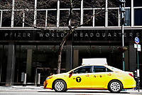 NEW YORK - NEW YORK - MARCH 23: A taxi drives in front of Pfizer World Headquarters on March 23, 2021 in New York. The Food and Drug Administration (FDA) says Pfizer's coronavirus vaccine can be stored in normal freezers for two weeks, instead of storage at ultra-cold temperatures. (Photo by John Smith/VIEWpress)