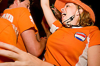 Netherlands fan Lianne Schuur cheers during her team's match against the Ivory Coast at Tonic, a New York City nightclub, on June 16, 2006.<br /> <br /> The World Cup, held every four years in different locales, is the world's pre-eminent sports tournament in the world's most popular sport, soccer (or football, as most of the world calls it).  Qualification for the World Cup is open to any country with a national team accredited by FIFA, world soccer's governing body. The first World Cup, organized by FIFA in response to the popularity of the first Olympic Games' soccer tournaments, was held in 1930 in Uruguay and was participated in by 13 nations.    <br /> <br /> As of 2010 there are 208 such teams.  The final field of the World Cup is narrowed down to 32 national teams in the three years preceding the tournament, with each region of the world allotted a specific number of spots.  <br /> <br /> The World Cup is the most widely regularly watched event in the world, with soccer teams being a source of national pride.  In most nations, the whole country is at a standstill when their team is playing in the tournament, everyone's eyes glued to their televisions or their ears to the radio, to see if their team will prevail.  While the United States in general is a conspicuous exception to the grip of World Cup fever there is one city that is a rather large exception to that rule.  In New York City, the most diverse city in a nation of immigrants, the melting pot that is America is on full display as fans of all nations gather in all possible venues to watch their teams and celebrate where they have come from.