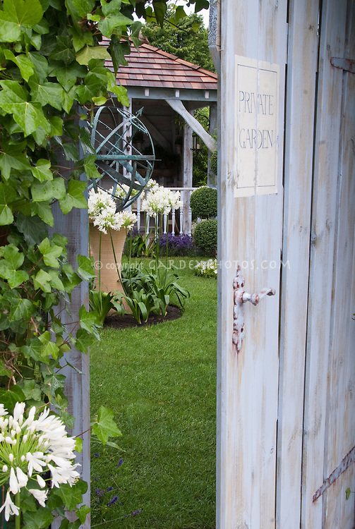 Secret garden door into lawn, gazebo, sundial, climbing ivy vine, agapanthus, access into private world, gaining admission to lovely backyard landscaping . Board and batten door