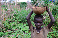 ETHIOPIA, Gambela, village Gog Dipach, girl with bowl with maize / AETHIOPIEN, Gambela, Dorf GOG DIPACH der Ethnie ANUAK, Maedchen mit Schale mit Mais  im Feld