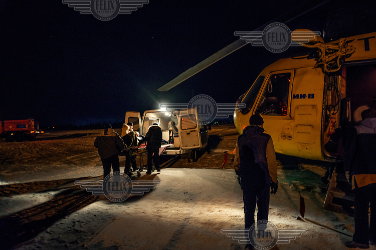 A patinet is loaded into an ambulance for the 10 minute drive to hospital after arriving on a helicopter at the airport.