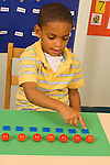 Piaget Preoperational child conservation of number boy counting items in equal rows to determine if there are the same number items have not yet been spread out vertical more in series available
