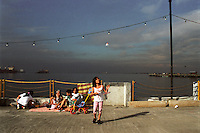 """A family picnicking on the """"Boardwalk"""" in Rizal Park built over the rocky beach of Manila Bay. Rizal Park is the largest park in Manila, Philippines named after national hero Jose Rizal. 17 November 2002"""