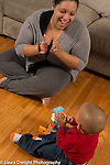 18 month old toddler boy building block tower, mother clapping and toddler joining in