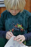 Kinder basteln ein Fensterbild mit Blüten, Junge zieht Schnur durch das Loch in den Ecken des Pergamentpapiers