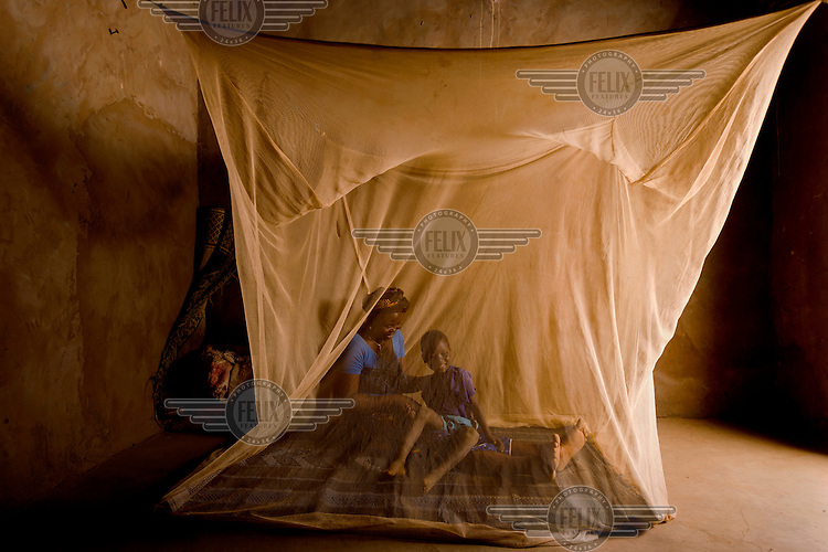 Inoussa Ouedraogo (4) and his mother, Minata Ouedraogo (38), under the mosquito net they share at their home in the village of Songodin. Mosquito nets greatly decrease the incidence of malaria by reducing the risk of being bitten by the nocturnal female Anopheles mosquito, which carries the malaria parasite.