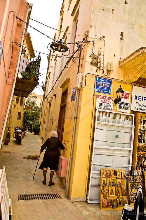 An elderly women walks down an alley in the residential quarters of Chania.