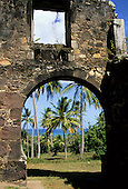 Salvador, Bahia State, Brazil; Castelo d'Avila, Praia do Forte, Costa do Sauipe resort; old stone arch with palm trees and blue sea.