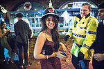 """© Joel Goodman - 07973 332324 . 19/12/2015 . Manchester , UK . A woman borrows a constable's helmet . Revellers in Manchester enjoy """" Mad Friday """" - also known as """" Black Eye Friday """" - the day on which emergency services in Britain are typically at their busiest , as people head out for parties and drinks to celebrate Christmas . Photo credit : Joel Goodman"""