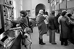 Post Office 1980s London UK. People filling in forms selecting leaflets. Mother and child going to the Post Office 1981