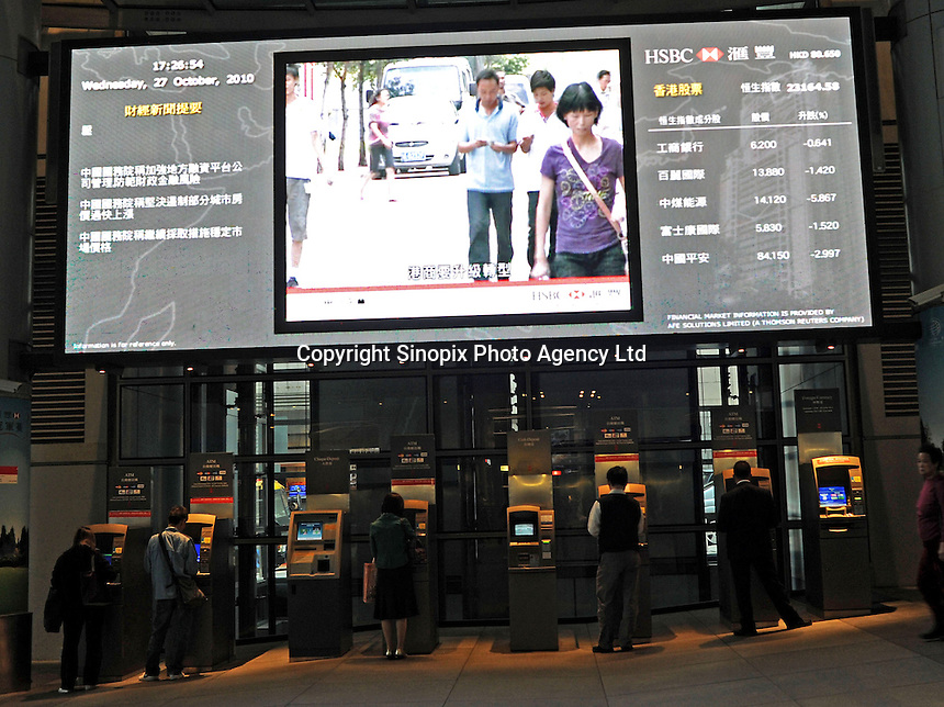 People using the ATM of HSBC in Central, a large-sized screen placed above the ATMs which indicates the stock prices, Hang Seng Bank Index (HSI) and financial news of the day, Hong Kong, China. HSBC is the world's largest company and the world's largest banking group. .