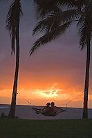 Couple kissing in hammock at sunset under palm trees in front of the ocean, Alii Beach park, North Shore of Oahu