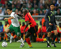Referee Shamsui Maidin watches Omar Bravo (19) of Mexico and Mendonca (14) of Angola battle for the ball. Mexico and Angola played to a 0-0 tie in their FIFA World Cup Group D match at FIFA World Cup Stadium, Hanover, Germany, June 16, 2006.