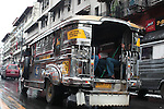 A jeepney drives on a street in downtown Manila. These exhaust-belching rattletraps crowd the streets of nearly every city in the Philippines. Initially built from jeeps left over behind by U.S. troops in World War II, they are one of the most common forms of local transport. June 10, 2011.