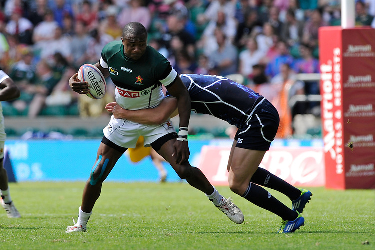 Tangai Nemadire of Zimbabwe is tackled by Adam Ashe of Scotland during the iRB Marriott London Sevens at Twickenham on Sunday 13th May 2012 (Photo by Rob Munro)