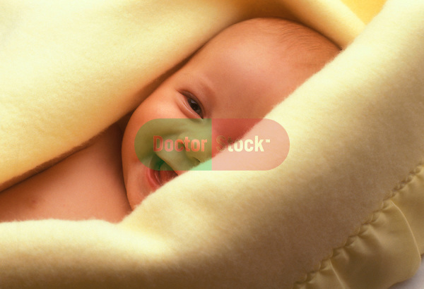 happy, laughing newborn baby wrapped in warm yellow blanket
