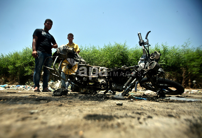 Palestinians look at a burnt out motorcycle that was destroyed in an Israeli air strike on north Gaza on June 18, 2012 killing two Palestinian men that were riding the motorbike near the Israeli border at the time. Witnesses identified the two men as members of the radical Islamic Jihad movement. Photo by Ali Jadallah