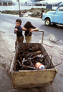 Children collect garbage in Bogota, Colombia - Child labor as seen around the world between 1979 and 1980 - Photographer Jean Pierre Laffont, touched by the suffering of child workers, chronicled their plight in 12 countries over the course of one year.  Laffont was awarded The World Press Award and Madeline Ross Award among many others for his work.
