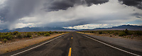 The yellow lines of a two lane highway, US Highway 50, under overcast skies in the middle of the high desert at the Utah Nevada border on a summer afternoon.