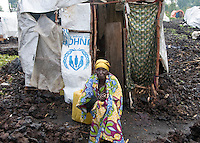 A woman sits outside her temporary shelter in the Kibati IDP (Internally Displaced Persons) camp.