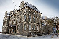 Pictured: Rear-side view of the old Police Station in Aberystwyth, Wales, UK. Wednesday 28 August 2019<br /> Re: Opened 1866, built by the Hafod Hotel Co as the Queens Hotel; architects, Hayward and Davies; builder George Lumley of Aberystwyth. Sold in 1877 and later converted to local government use; remodelled in1950 by G R Bruce, County Architect.<br /> Detached towards N end of the Promenade, with main entrance to side elevation in Albert Place and rear elevation to Queens Road.<br /> Hotel de Ville style. Asymmetrical 3-storey attic and basement snecked rubble 13-bay W (Promenade) elevation; stepped front with mostly vermiculated dressings, stock brick voussoirs, deep entablature and cornice and cill bands; buttresses to ground floor centre. Steep pitch mansard slate roof with truncated chimney stacks. Dormers with steep overhanging roofs and casement windows; paired to left. 3-bays advanced near the right hand end and with additional storey and splayed angles to 2nd floor (with small cast-iron parapets) and 3rd floor; also to top floor) with small cast-iron parapets) and 3rd floor; also to top floor at the corner. Sash windows, some paired; anthemion panelled cast-iron window box holder across central bays.