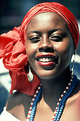 Salvador, Bahia State, Brazil. Beautiful Bahiana woman in a red headscarf wearing beads.