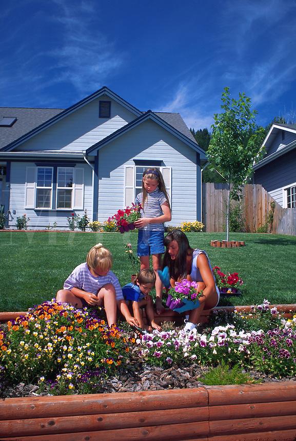 Mother and children planting annuals in garden