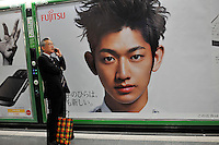 A man makes a phone call next to a Fujitsu advert featuring Japanese actor Eita in the Shinjuku district of downtown Tokyo, Japan..