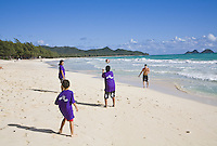 Kids playing football on the beach during a charity surfing event