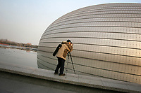 CHINA. Beijing. A photographer photographing the outside view of the Grand National Theatre. Designed by French architect Paul Andreu, The Grand National Theatre is located near Beijing's central Tian'anmen Square. It is an enormous glass and titanium tear-drop-like bubble structure surrounded by water. As China's top art performance center, it covers a total floor space of around 180,000 square meters, including 130,000 square meters for the main building and 50,000 square meters underground facilities. 2008.
