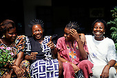 La Lope, Gabon. Four women laughing, sitting in front of a building.