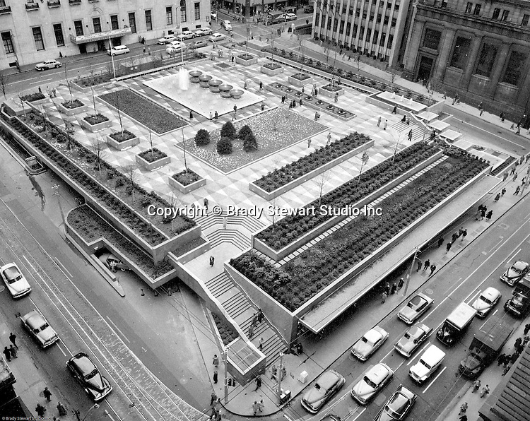 Pittsburgh PA:  View of opening day for Mellon Square Park taking from the Gimbels parking garage roof.  Mellon Square, built-in 1953-55 was designed by Mitchell & Ritchey, landscaped by Simonds & Simonds, and paid for by Mellon family foundations.  Rumor has it that the park was built to keep Alcoa Corporation from moving from Pittsburgh to New York City in the early 1950s.  Other buildings in the photo include William Penn Hotel and the Alcoa Building.