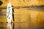 A young surfer walks studies the waves of the Atlantic while in the background the yellow red cliffs of Sagres reflect in the water of the Algarve region of Portugal.