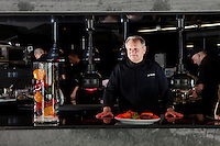 Joël Robuchon, chef and and restaurateur, poses for the photographer looking out from the open kitchen at Odyssey in the Hotel Metropole, Monte Carlo, Monaco, 22 May 2013. Odyssey, opened in spring 2013, is an exclusively alfresco dining experience and Joël Robuchon's third restaurant within the hotel.