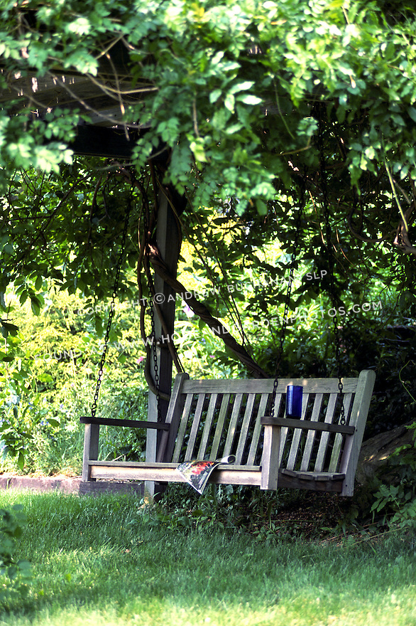 A wooden swing tucked under an arbor of wisteria offers a peaceful place for reflection.