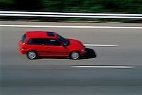 Speeding red car travelling on a highway.