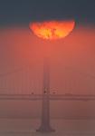 The sun rose in two a thin dark clad cover over the Bay Bridge, California.