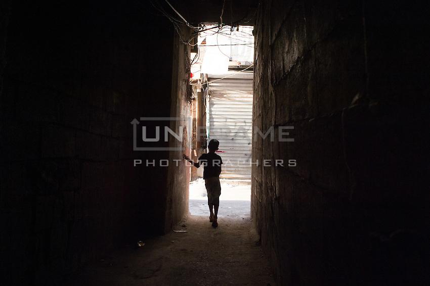 Young boy walking the streets of Shatila. Beirut. Lebanon, August 2015