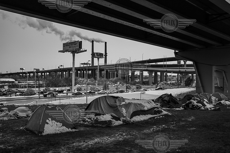 Snow partially covers tents in a homeless person's camp established under a viaduct.