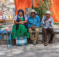 Tlacolula, Oaxaca, Mexico.  Tlacolula Plaza in front of Church, Capilla del Santa Cristo.  Zapotec Indians in Conversation.  Local Clothing Styles.