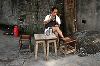 A man sits on furniture made of bamboo in the streets of a small village in southern Sichuan Province.