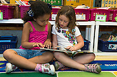 MR / Schenectady, NY. Zoller Elementary School (urban public school). Kindergarten classroom. Two students read book together in class. Left: girl, 6, Hispanic-American; Right: girl, 5. MR: Fue3, Cas12. ID: AM-gKw. © Ellen B. Senisi.
