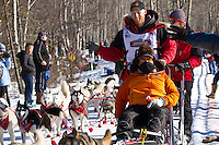 Danny Seavey and team run past spectators on the bike/ski trail during the Anchorage ceremonial start during the 2014 Iditarod race.<br /> Photo by Britt Coon/IditarodPhotos.com