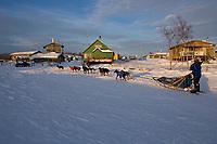 As the sun rises over frozen Yukon River Jessica Hendricks arrives in Kaltag 2006 Iditarod Western AK