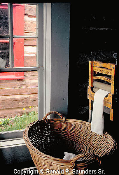 Interior detail of an early 20th century log cabin. Inside there is a clothes- ringer, dryer and wicker basket.