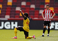 1st May 2021; Brentford Community Stadium, London, England; English Football League Championship Football, Brentford FC versus Watford; Joseph Hungbo of Watford kneels in support of anti-racism while Sergi Canos of Brentford stays standing before kick off