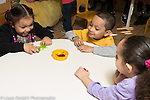 Education preschool 4 year olds boy and two girls playing game taking turns flipping plastic frogs into container